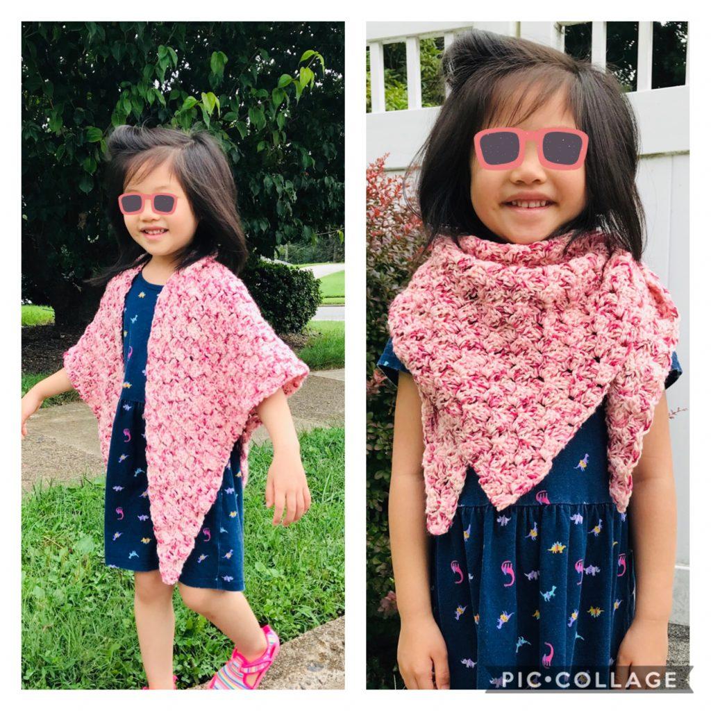 Little girl showcasing a pink crocheted triangular shawl